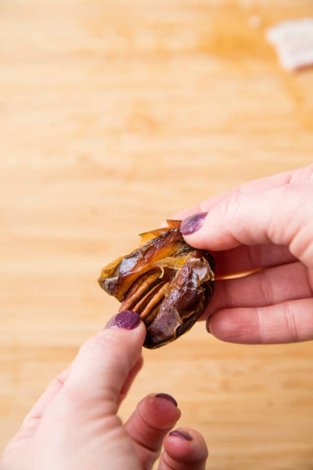 woman's hand stuffing a pecan into a date