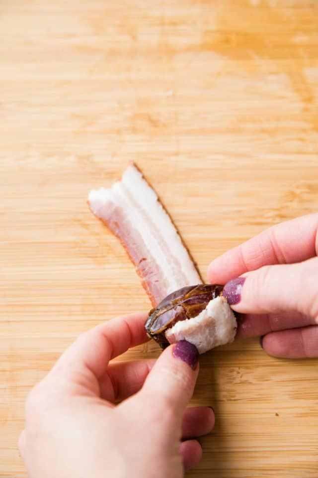 woman's hand rolling date in a strip of bacon