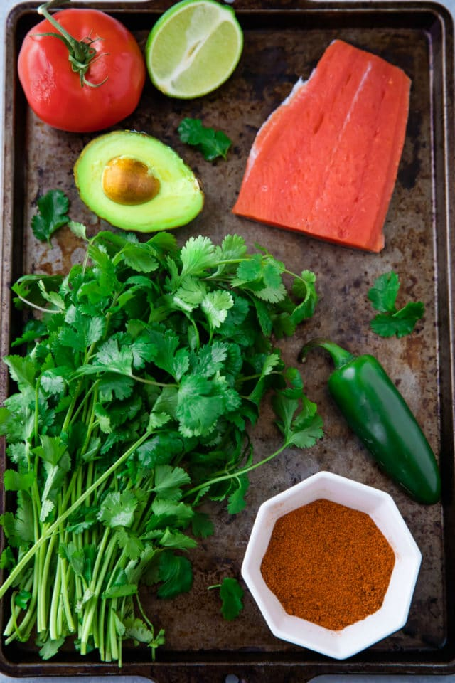 Ingredients on a baking sheet for pan seared salmon and avocado salsa