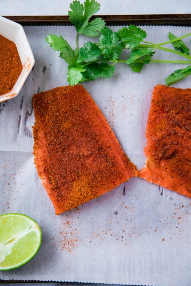 fresh salmon fillets seasoned with taco seasoning on parchment paper