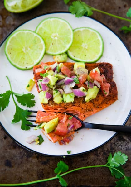 Pan Seared Salmon with Avocado Salsa on a white plate with a black fork taking a bite