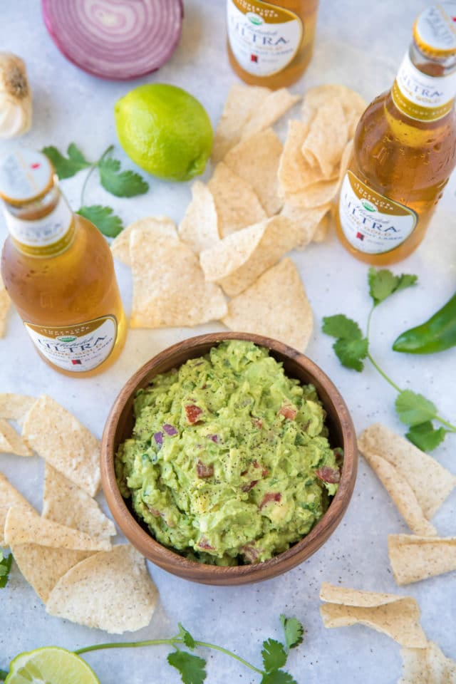 guacamole in a wooden bowl served with tortilla chips and beer