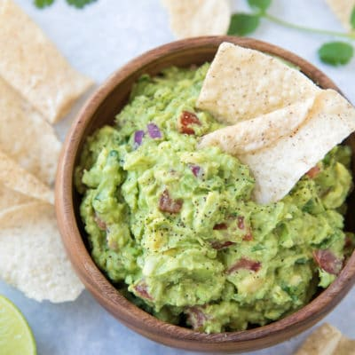 homemade guacamole in a wooden bowl served with tortilla chips