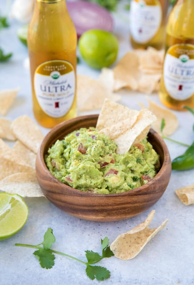 chips dipped in guacamole and served with beer