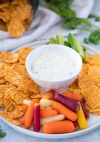 Ranch dip in a small white bowl on a platter being served with chips and veggies