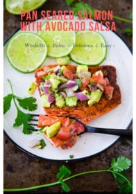 Pan Seared Salmon with Avocado Salsa on a white plate with lime slices and cilantro on the side