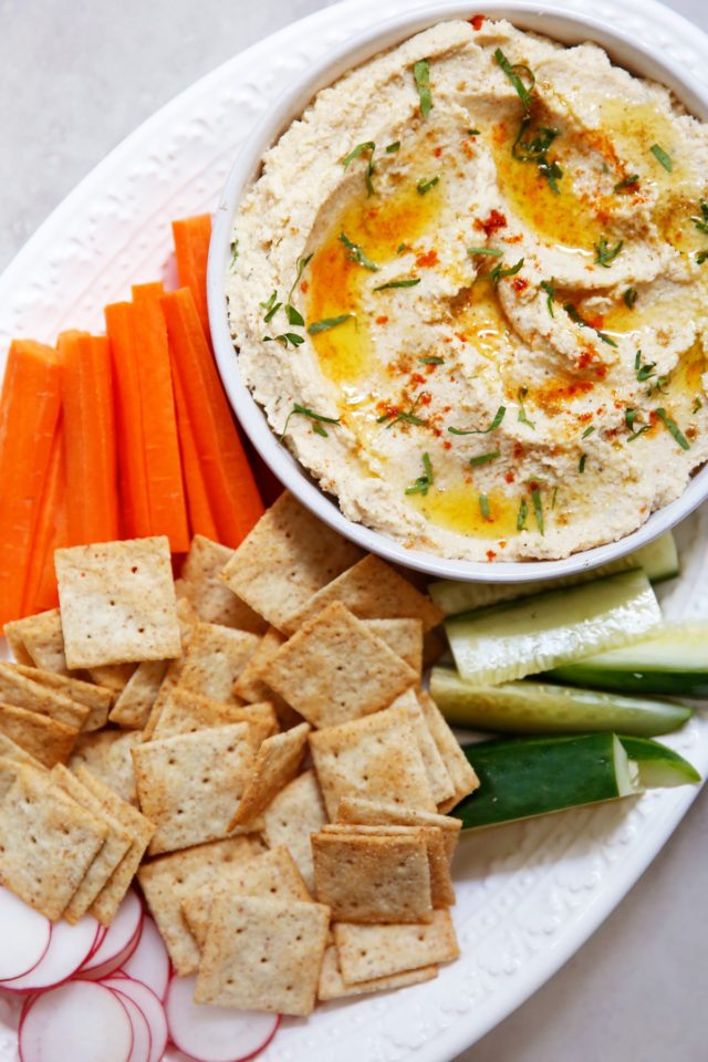 cauliflower hummus served in a white bowl with carrot sticks, cucumber and crackers