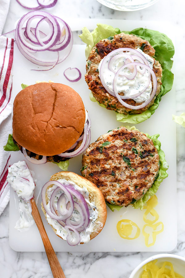 Greek Turkey Burgers topped with red onion and tzatziki sauce