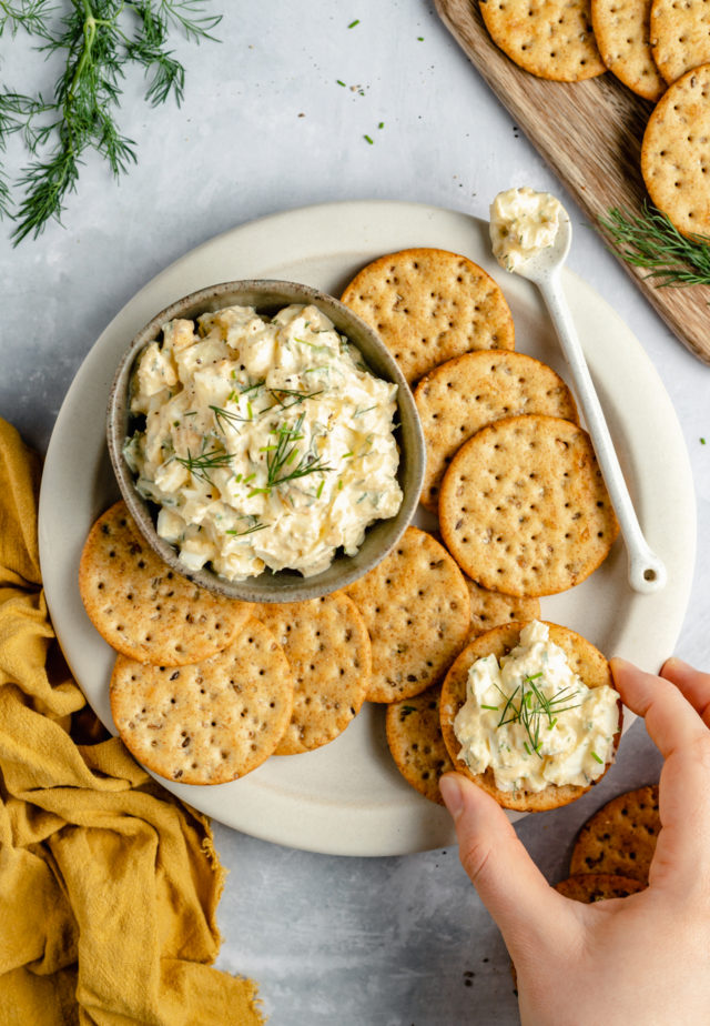 woman holding a cracker that is topped with egg salad