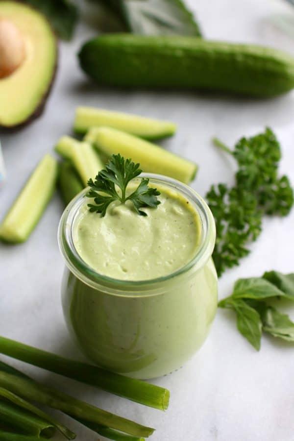 Green Goddess Dressing in a glass jar garnished with fresh parsley
