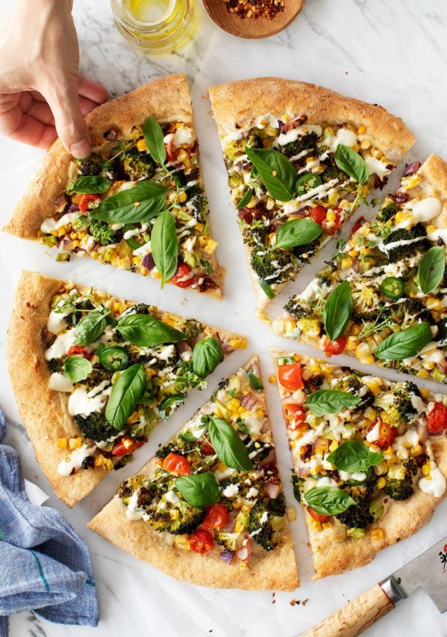 colorful pizza sliced with a woman's hand pulling one piece away
