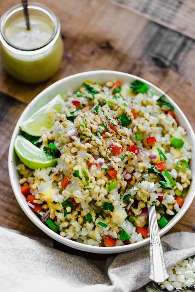 cauliflower rice salad in a large white serving bowl with lime slices on the side