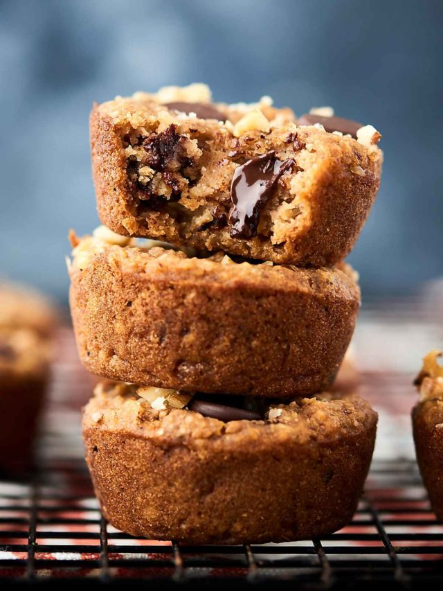 chocolate chip muffin with a bite taken out stacked on top of two other muffins
