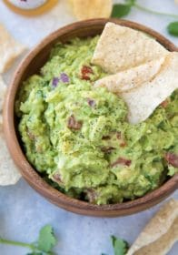 homemade guacamole in a wooden serving bowl with a tortilla chip