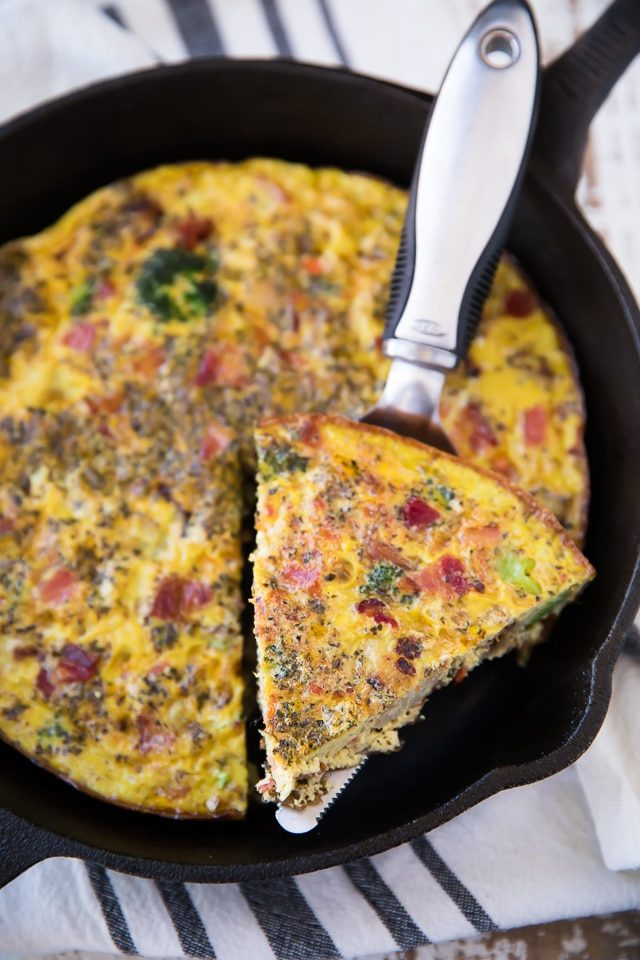 frittata in a cast iron skillet being served with a metal pie server