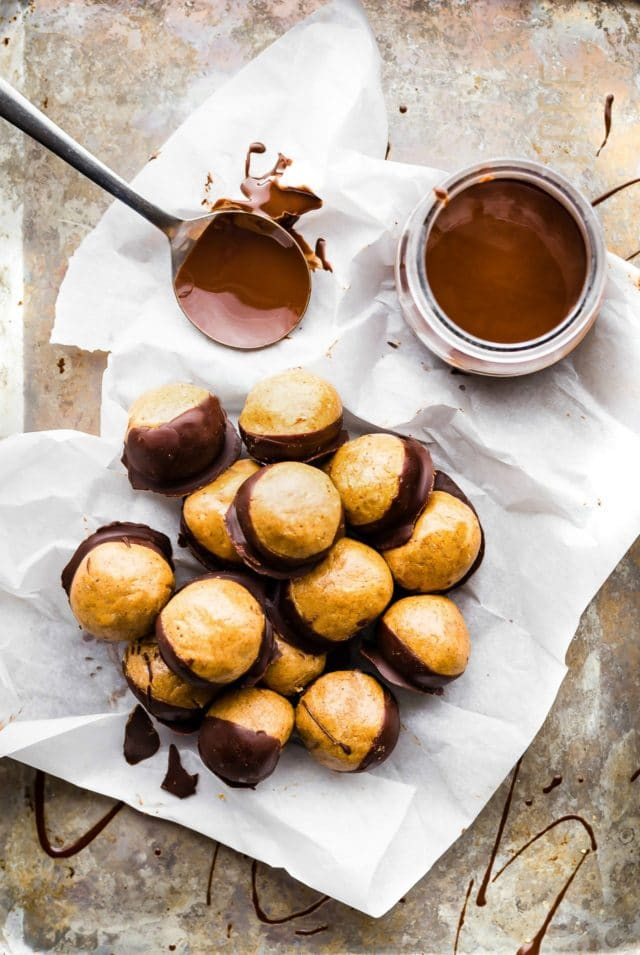 Peanut Butter Buckeyes on parchment paper near a jar of chocolate