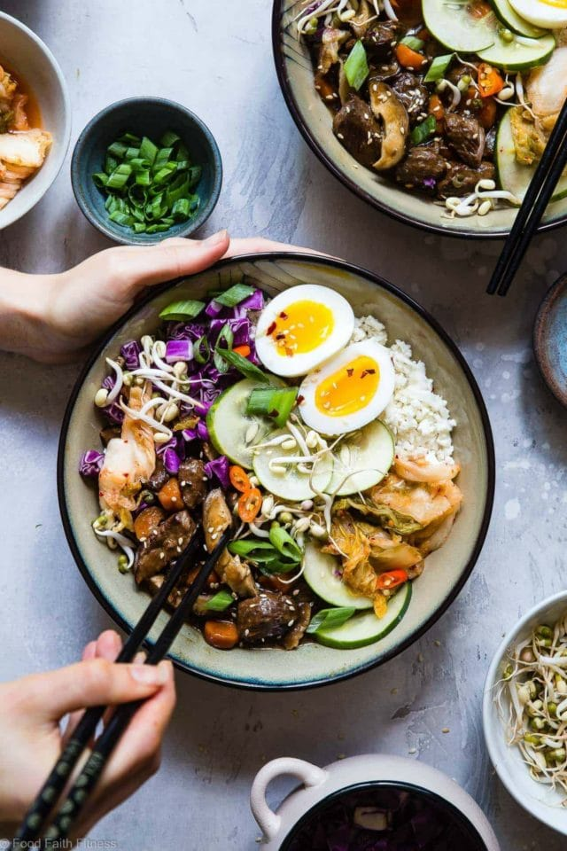 slow cooker whole30 paleo korean beef stew in a bowl with a woman's hand around it with chopsticks