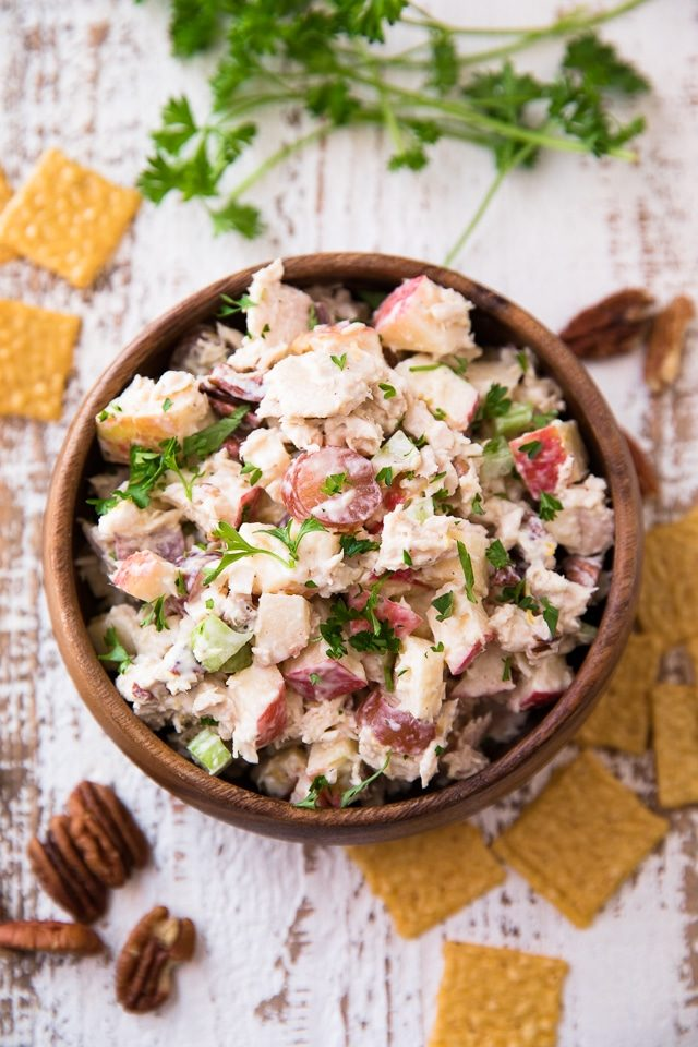 Waldorf Tuna Salad in a wooden serving bowl with crackers scattered around