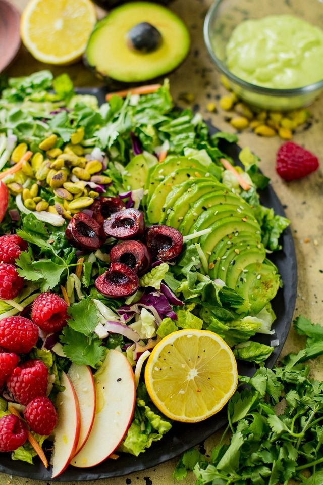 large salad topped with sliced avocado, raspberries, cherries and sliced apple