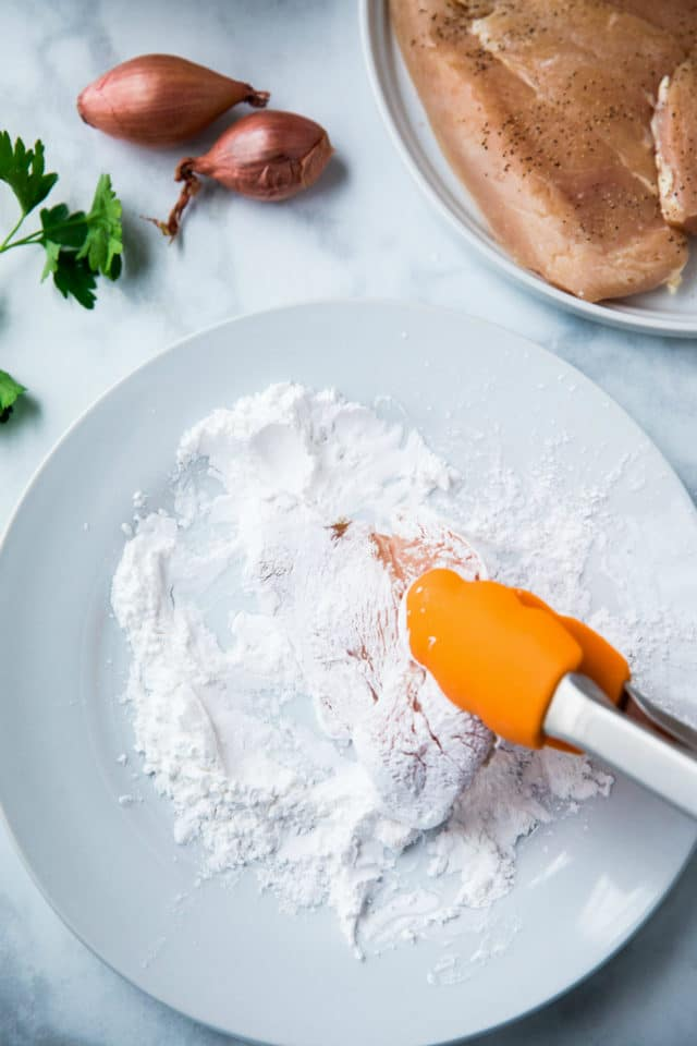 dredging chicken into flour using tongs