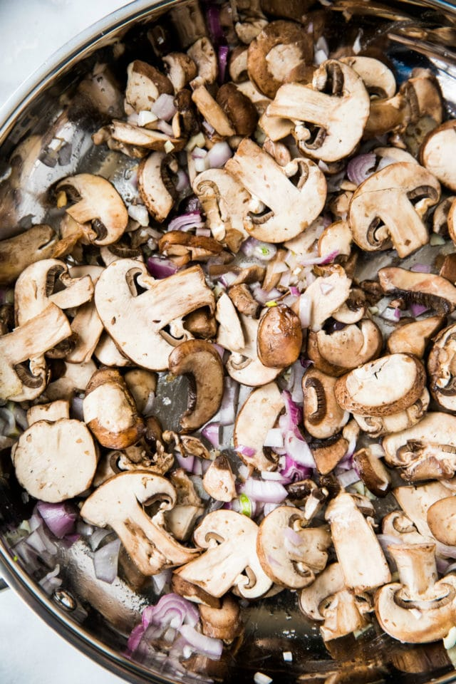 mushrooms cooking in a large skillet