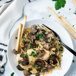 white bowl filled with Chicken Marsala and pasta with a black fork