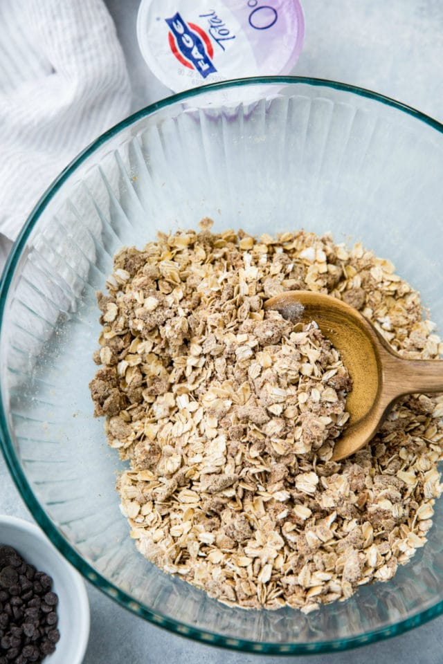 granola ingredients mixed with a wooden spoon in a large glass mixing bowl