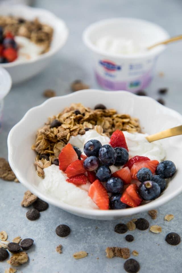 yogurt fruit granola bowl with gold spoon