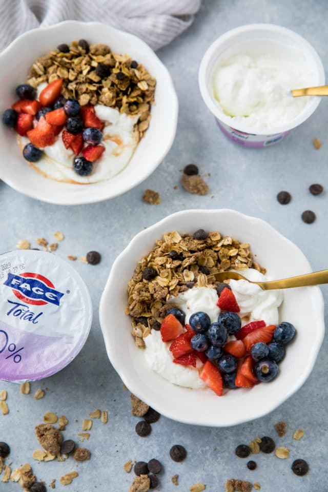 granola and yogurt in white bowls topped with blueberries and strawberries