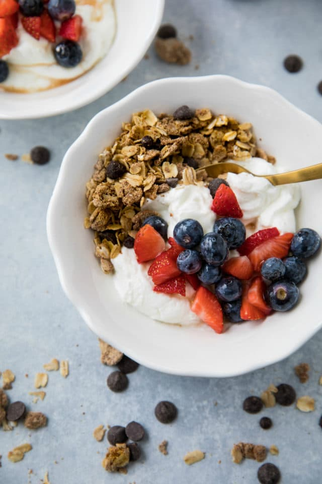 yogurt and granola in a white bowl topped with berries and served with a gold spoon