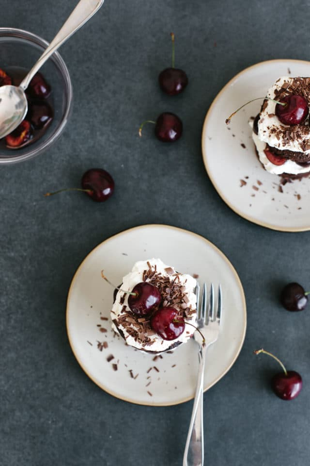 little chocolate cakes on white plates, topped with whipped cream and cherries