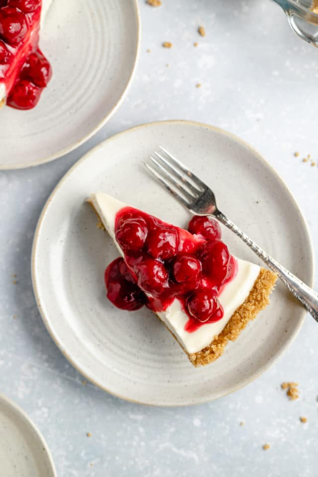 slice of no-bake cheesecake served with cherry pie filling on a small white plate