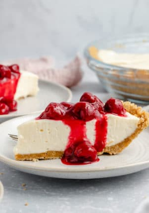slice of cream cheese pie topped with cherries