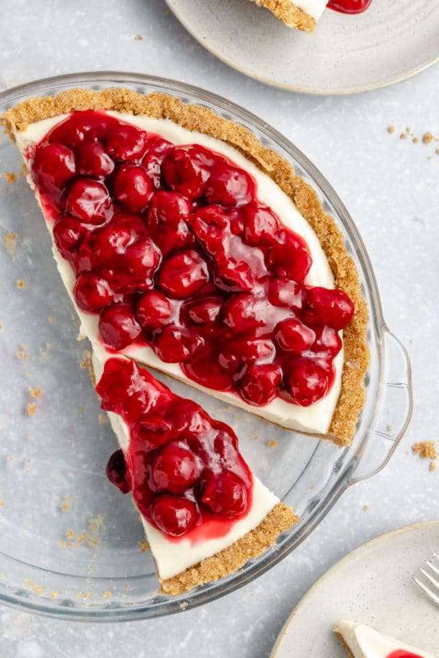 cream cheese pie cut into slices and topped with cherry pie filling