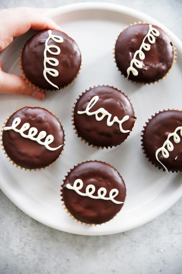 homemade hostess cupcakes on a white plate with a hand grabbing one