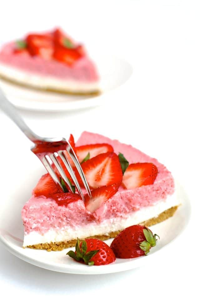 a piece of Strawberry Cheesecake on a white plate topped with fresh strawberries