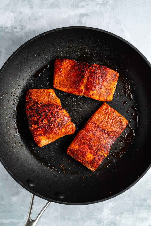salmon cooking in a large skillet