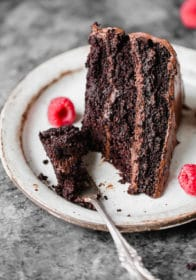 chocolate cake on a white plate with a bite on a fork