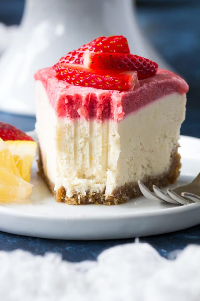 strawberry cheesecake on a white plate with sliced lemon