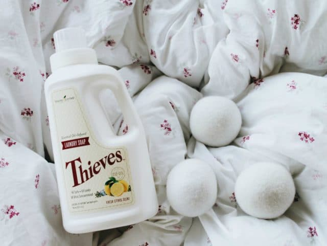 Theives laundry detergent with laundry balls laying on a fluffy comforter