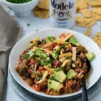 chili topped with diced avocado and tortilla strips and served with beer