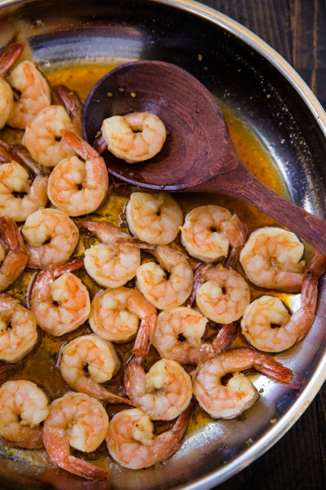 shrimp cooking in a large skillet with a wooden spoon