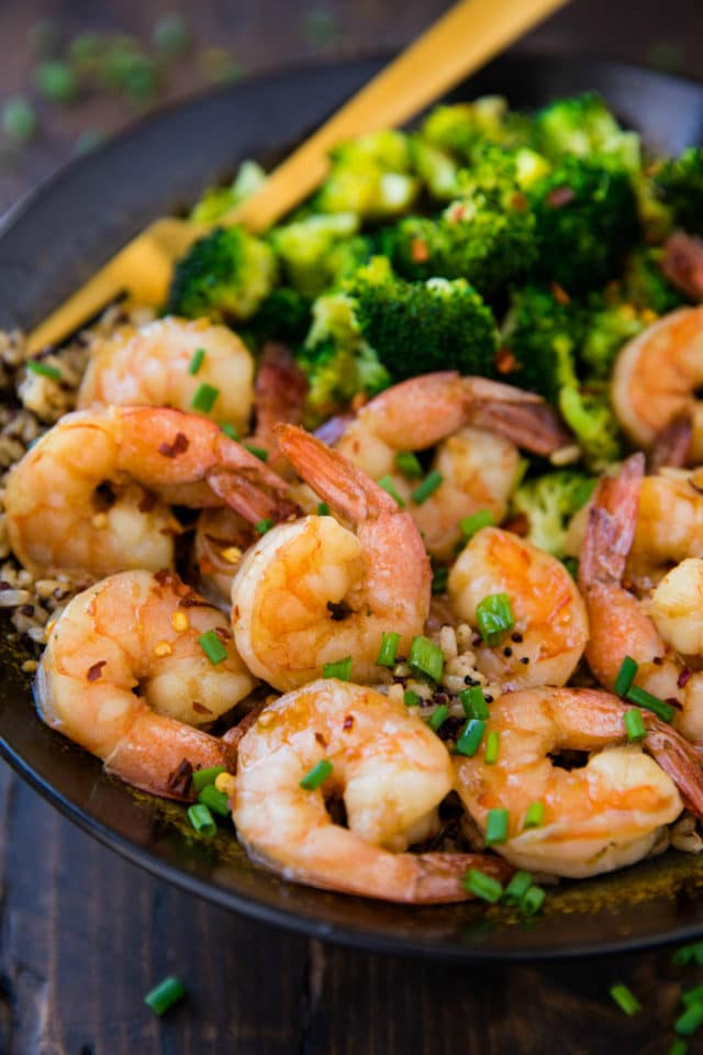 honey garlic shrimp served with brown rice and broccoli in a black bowl with a gold fork