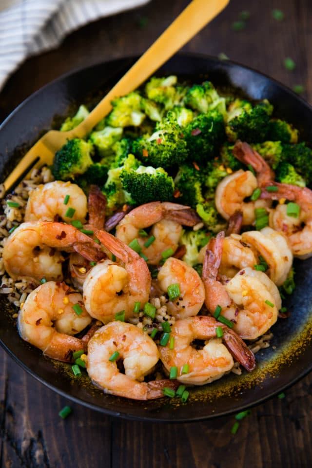 cooked shrimp in a black bowl with brown rice and broccoli