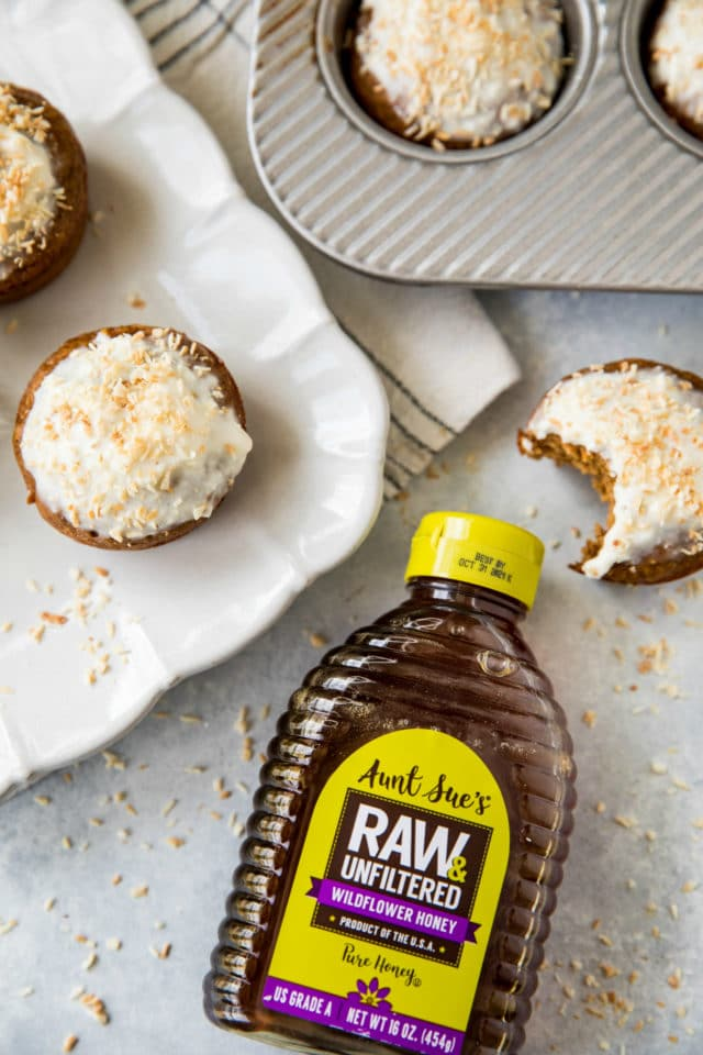 bottle of honey near muffins that have a white icing