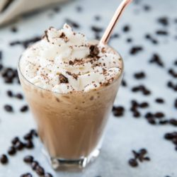mocha shake topped with whipped cream and served with a rose gold straw