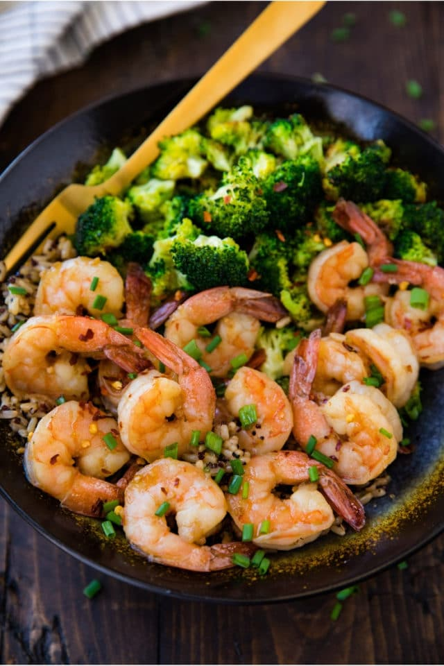 HealthyHoney Garlic Shrimp served with rice and broccoli in a large black bowl