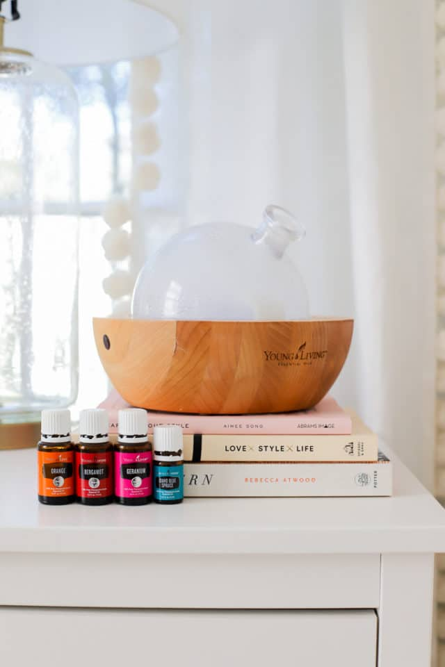 essential oils diffuser sitting on books with oils in front