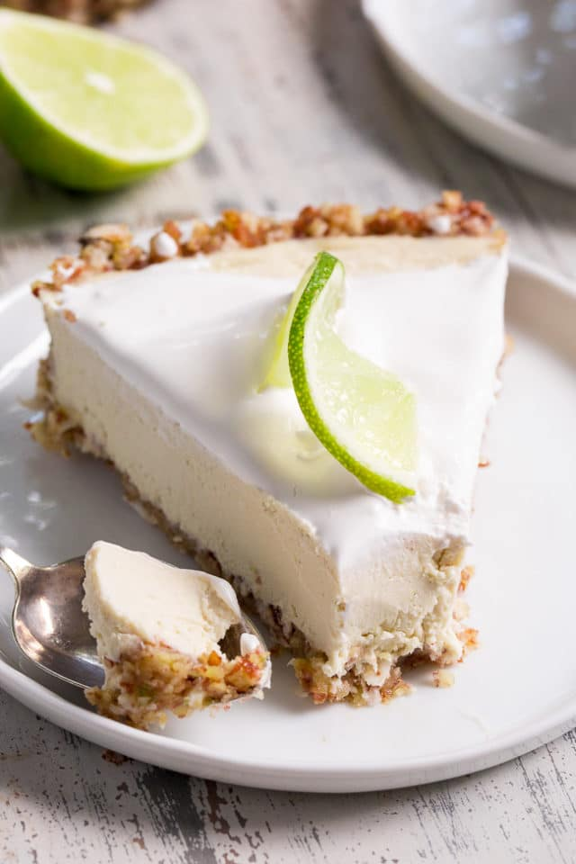 key lime cheesecake on a white plate garnished with a lime slice and a spoonful to the side