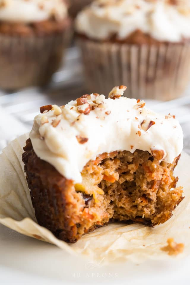 Paleo Carrot Cake Cupcakes on a muffin liner with one bite taken out
